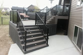 Stairs and composite deck with glass railings.